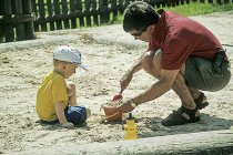 father & son making sandcastles in a sand pit.jpg