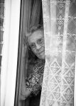 vulnerable elderly woman looking out of the window feeling worried1.jpg